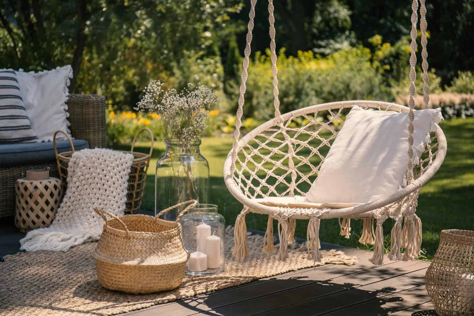 A beige string swing with a pillow on a patio. Wicker baskets, a