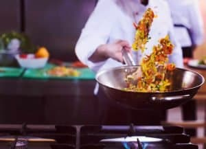 chef flipping vegetables in wok