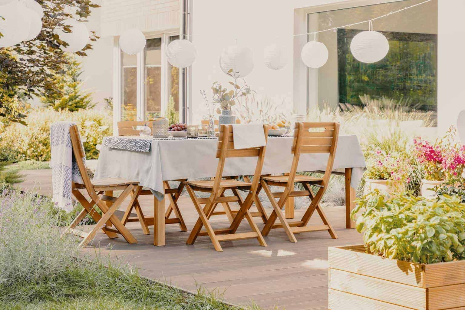 Outdoor dining room with wooden garden furniture set with table and chairs
