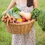 Pretty woman with basket of veg on a sunny day