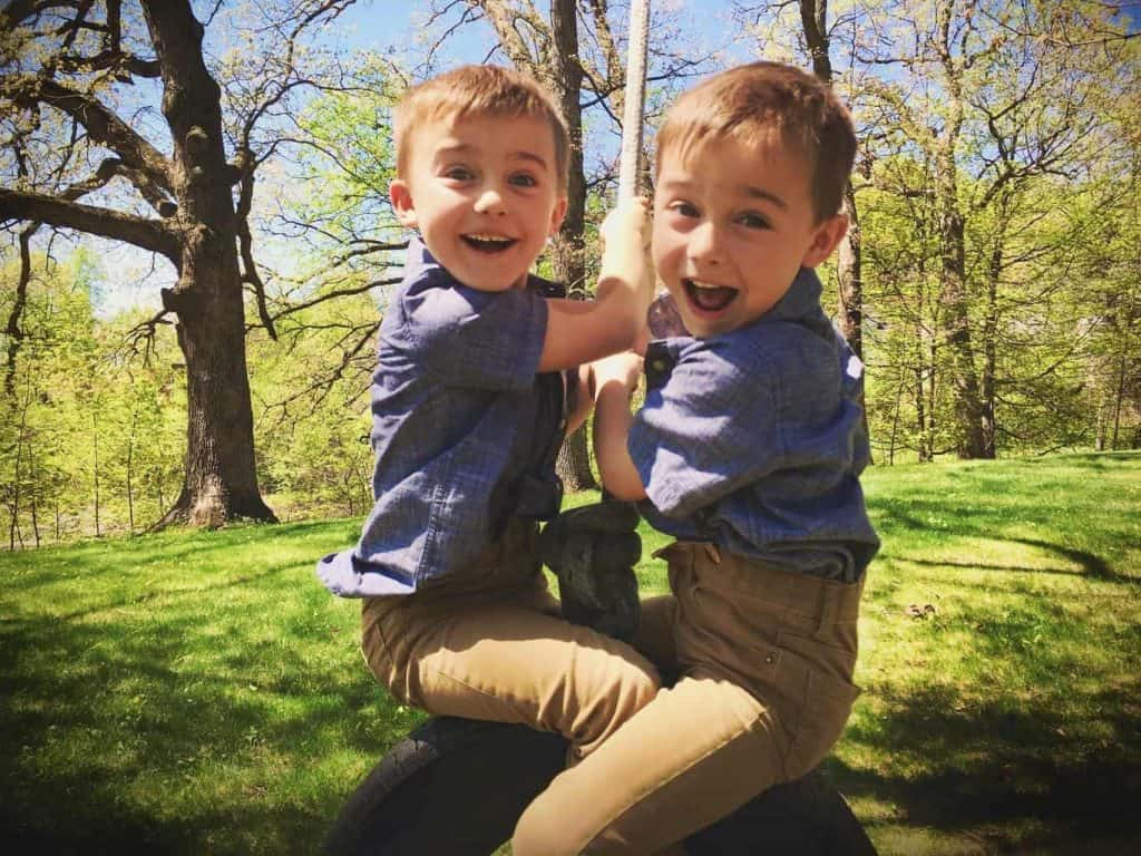 Playing on a tire swing happy boys